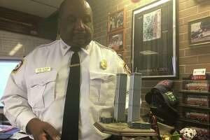 New Haven Fire Chief John Alston Jr. with Sept. 11 mementos in his office in New Haven's Fire Headquarters on Grand Avenue. Alston was a 40-year-old Jersey City firefighter on Sept. 11, 2001, and was at ground zero soon after the plans struck the World Trade Center's twin towers. He knew several New York City firefighters and one Jersey City dispatcher who died in the attacks.
