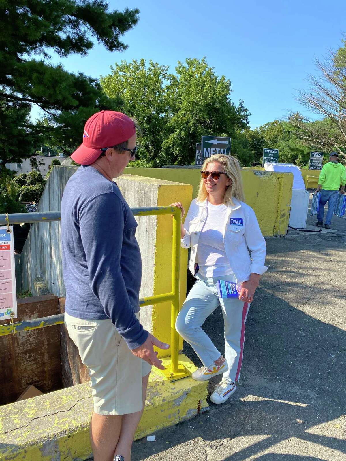 A flood-effected resident shows first selectman candidate Tara Ochman a video of previous flooding during a tour of residential damage.