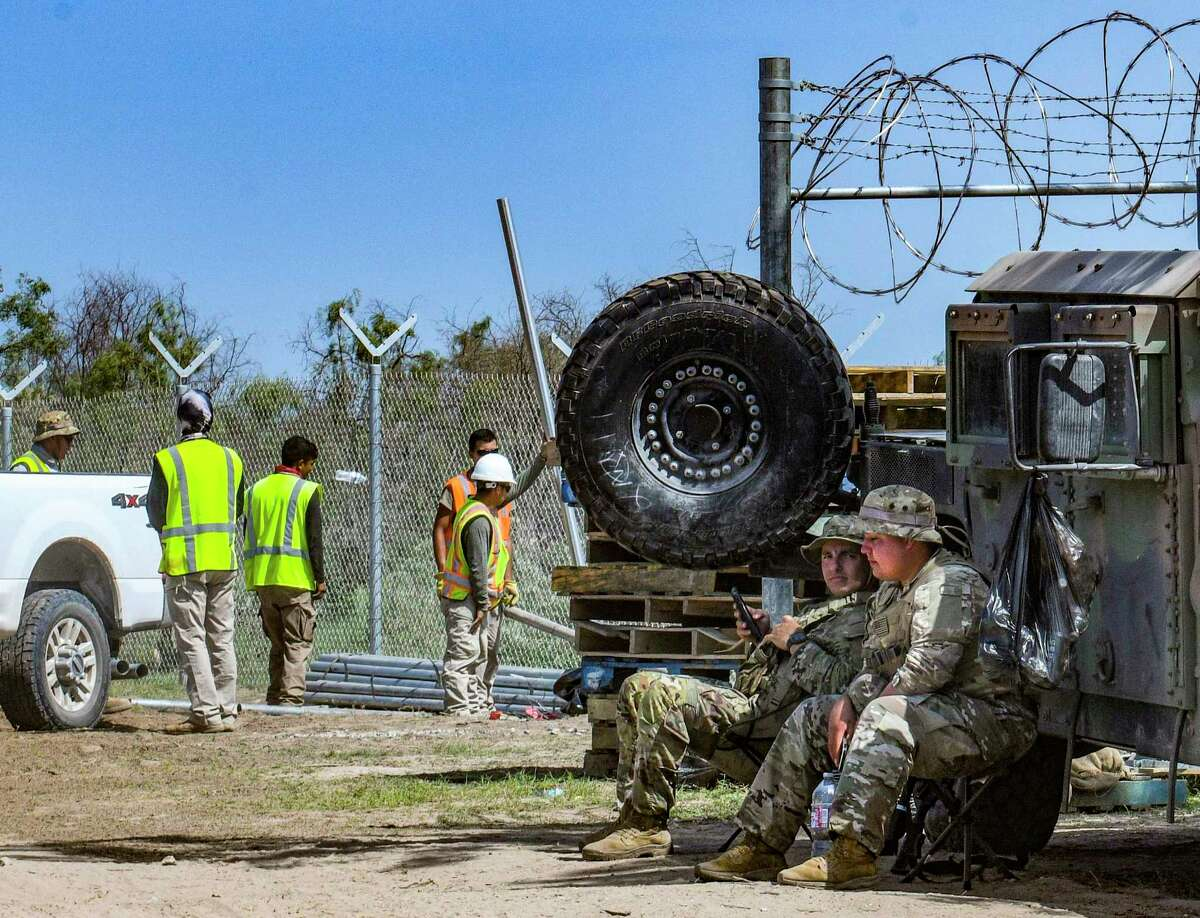 Members of the Texas National Guard take shelter from the heat by their vehicle as a crew installs a fence on the border at Del Rio earlier this summer as part of Gov. Greg Abbott's border security efforts.