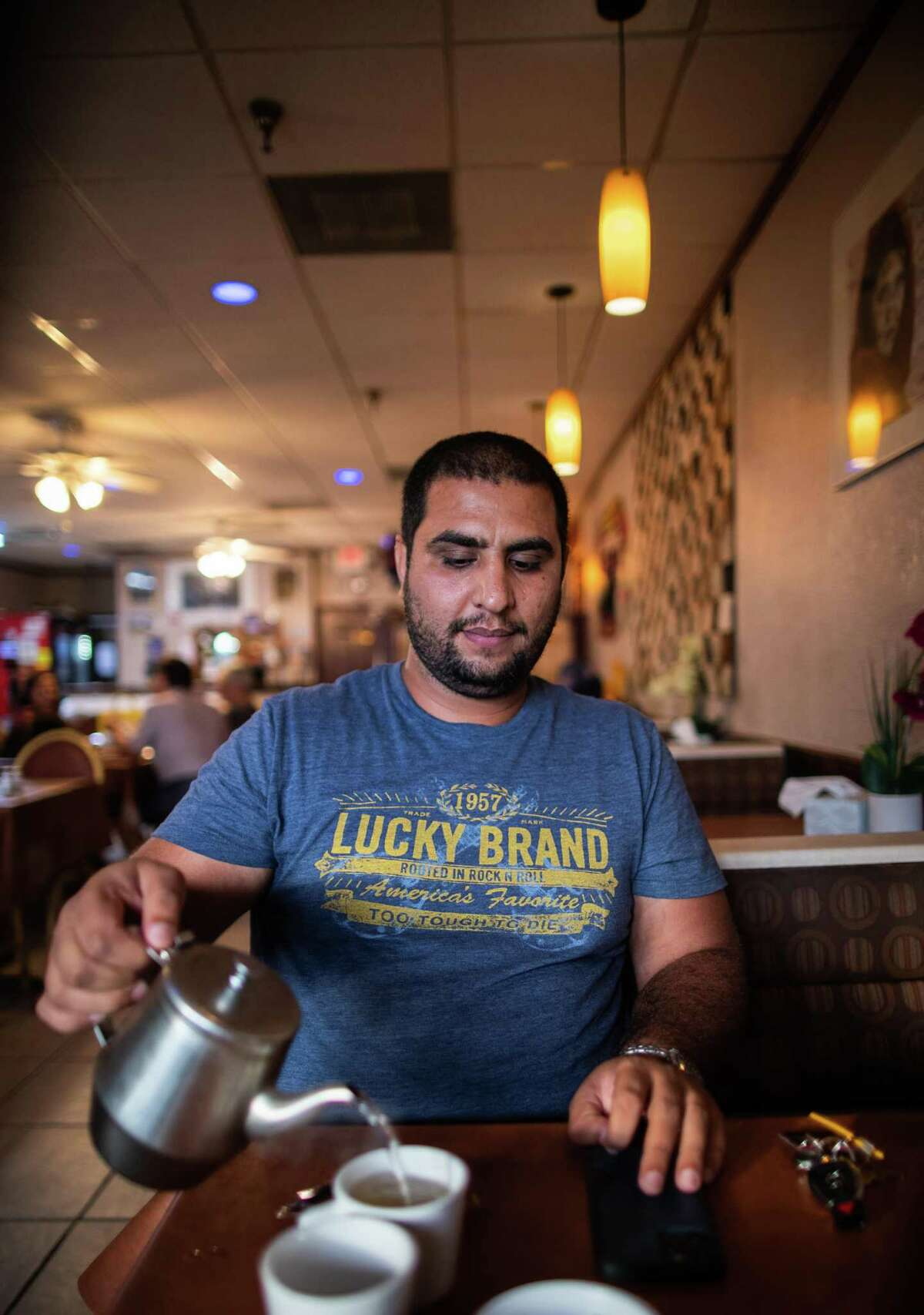 Ahmad Rashad, an Afghan-American and former translator in Afghanistan for U.S. soldiers pours tea for himself at the Afghan Village Restaurant, Tuesday, Sept. 7, 2021, in Houston. Rashad was about 10 years old when a series of terrorist attacks took place in U.S. soil on Sept. 11, 2001.