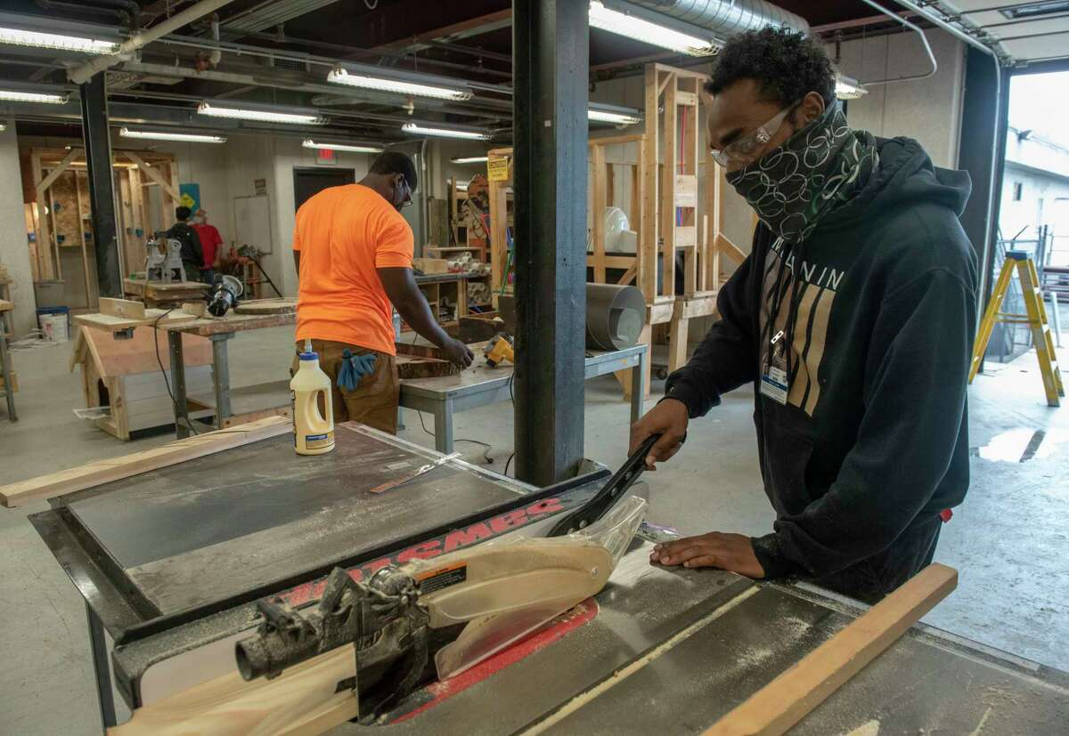 Students Jonathan Mays, center, and Kevon Jones are seen working of projects in the building trade classroom at the Capital District Educational Opportunity Center on Thursday, Sept. 9, 2021 in Troy, N.Y.