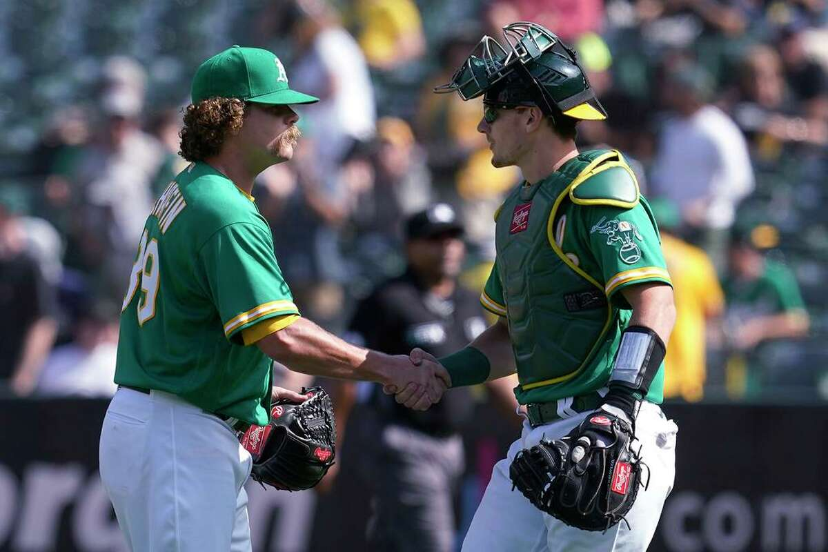 Oakland Athletics pitcher Andrew Chafin, left, celebrates with catcher Sean Murphy after the Athletics defeated the Chicago White Sox in a baseball game in Oakland, Calif., Thursday, Sept. 9, 2021. (AP Photo/Jeff Chiu)