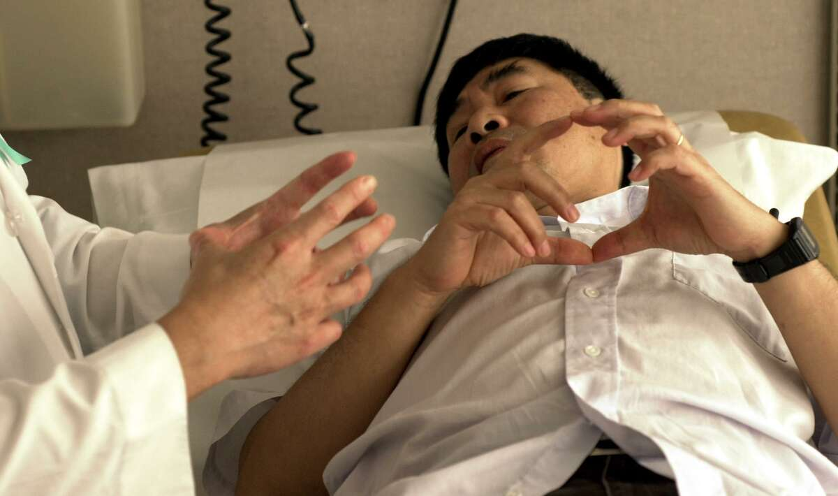 A doctor shows with his hands how large the cancer on a patient's liver was.