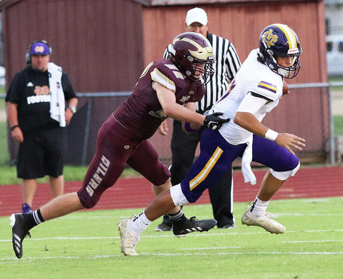 EA-WR's Lucas Brown (left) runs down CM quarterback Bryer Arview for a sack during the first half last Friday at Memorial Stadium in Wood River.