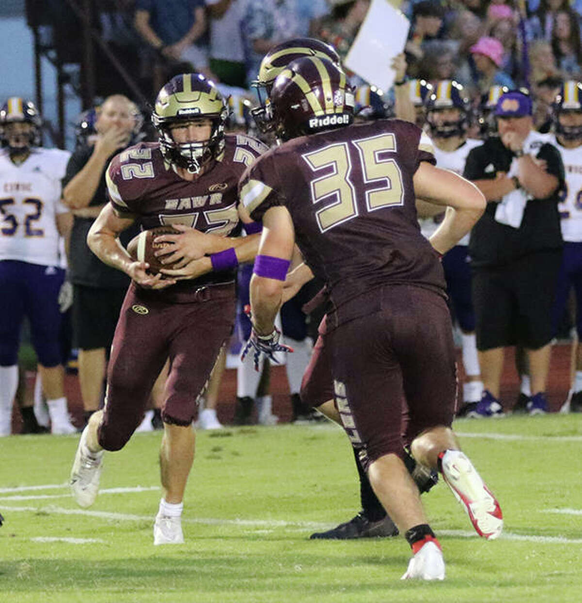 EA-WR running back Seth Slayden takes a handoff before handing off to Zach Oster (35) on an inside reverse during the first half last Friday night in Wood River.