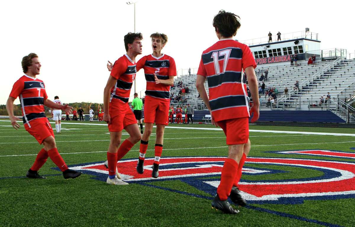 Big Rapids senior Brendan Pippin (second from left) is embraced byAden Herron (far left), Lukas Timm (second from right) and Murdoch Macdonald after scoring a late, game-tying penalty kick during Thursday's game against Fremont at Cardinal Stadium. (Pioneer photo/Joe Judd)