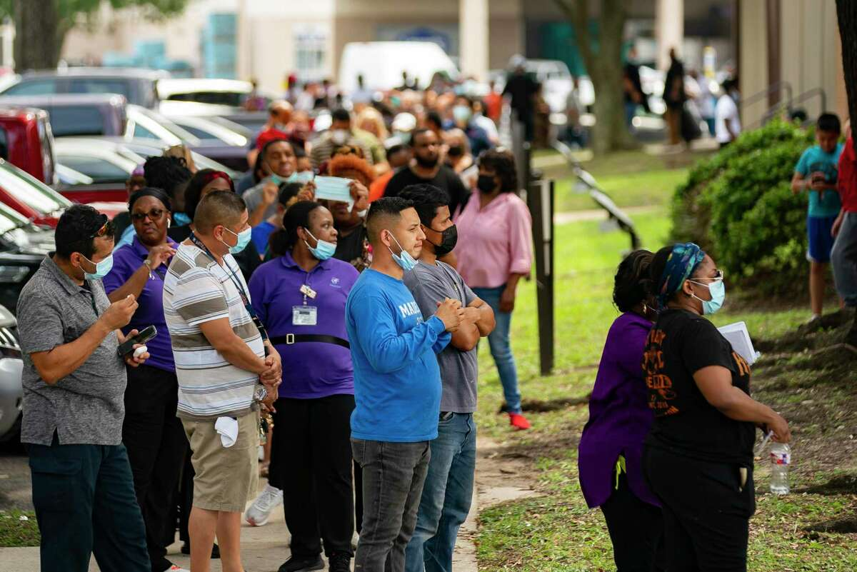 A line of people waiting for assistance applying for both the Harris County Recovery Assistance and the Houston-Harris County Emergency Rental Assistance program wait outside of the IBEW Local 716 building, Tuesday, Aug. 3, 2021, in Houston.