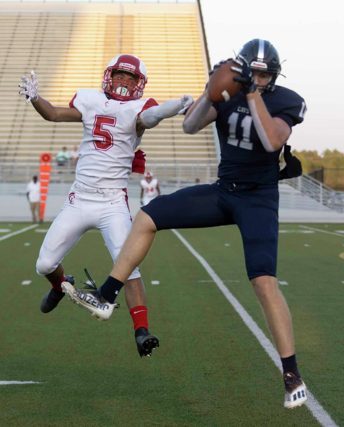 College Park tightend Cody Mladenka (11) catches a pass despite pressure from Cypress Lakes defensive back Nicholas McDonald (5) during the first quarter of a non-district football game at Woodforest Bank Stadium, Thursday, Sept. 9, 2021 in Shenandoah.