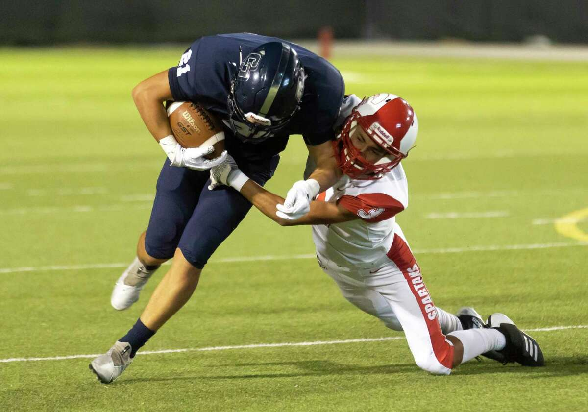 College Park linebacker Jessie Cochran (21) is dragged down by Cypress Lakes defense during the fourth quarter of a non-district football game at Woodforest Bank Stadium, Thursday, Sept. 9, 2021 in Shenandoah.