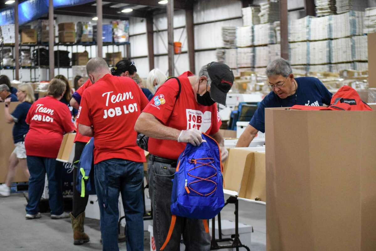 Representatives from Ocean State Job Lot help stuff backpacks with donated school supplies in Foxborough, MA.