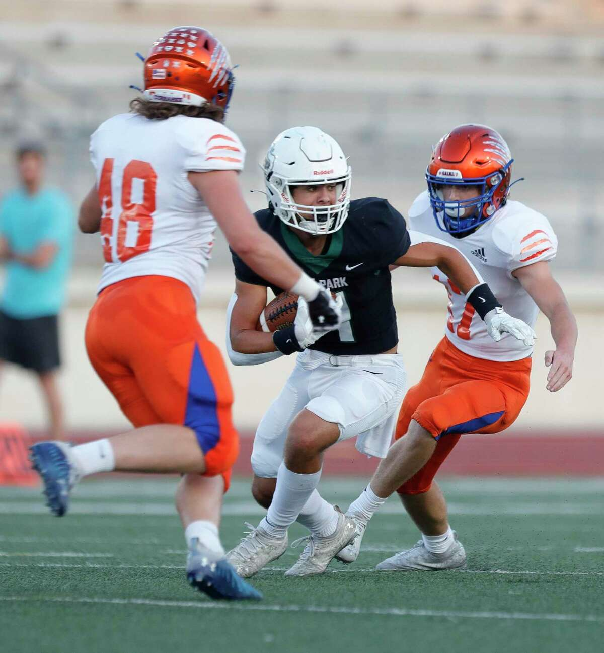 Kingwood Park wide receiver Pierce Richards (4) turns after making a catch between Grand Oaks linebacker Noah Langridge (48) and defensive back Logan Telfer (17) during the first quarter of a non-district high school football game at Turner Stadium, Thursday, Sept. 9, 2021, in Humble.