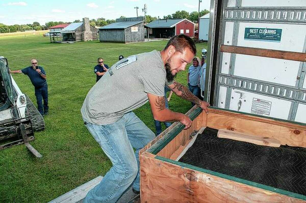 Kevin Christopherson with the traveling World War II memorial unloads his truck Thursday afternoon. The memorial will be up through Sunday at Prairie Land Heritage Museum.