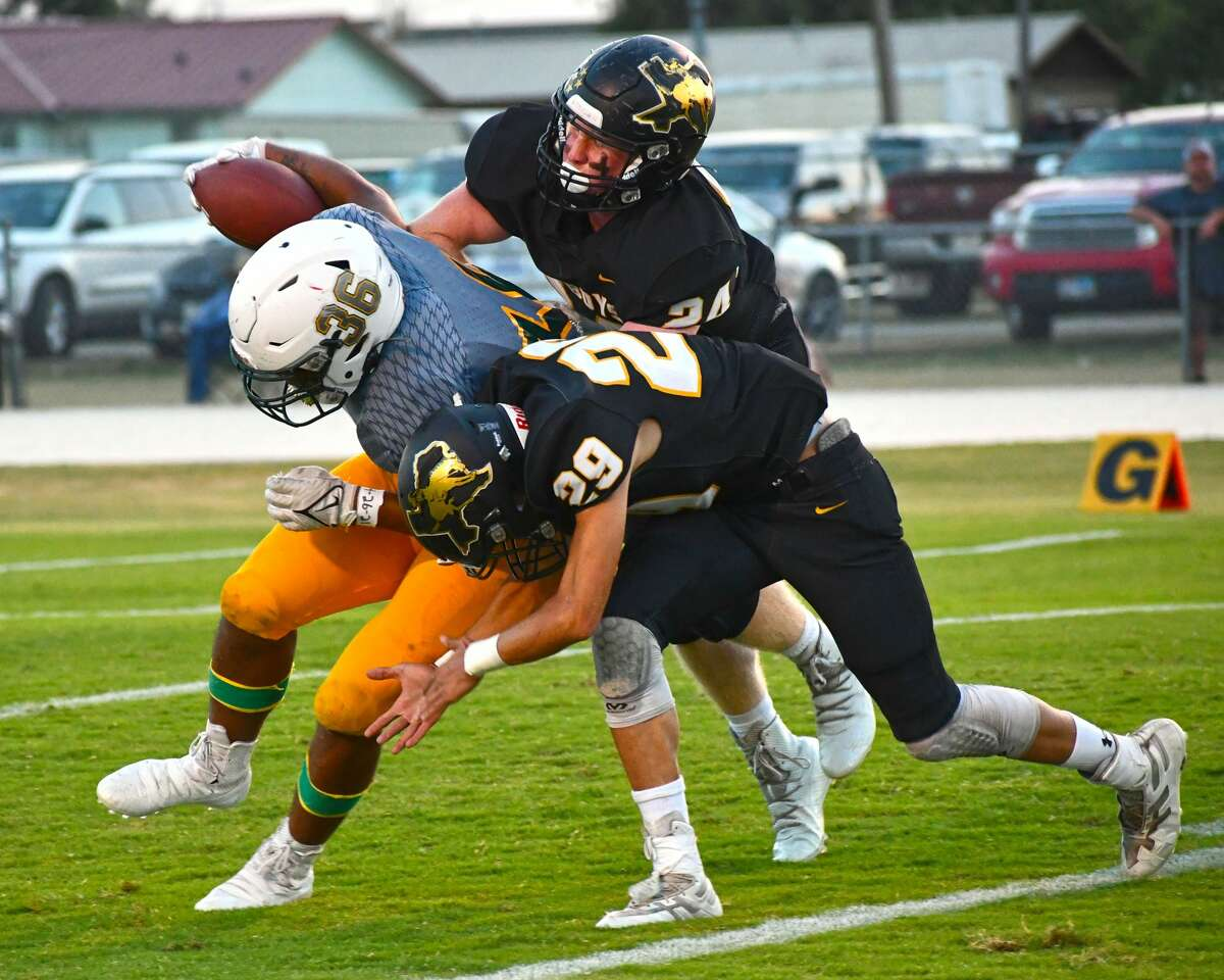 Happy defenders Kyton Johnston (24) and Jimmy Reyes (29) team up to take down Springlake-Earth ball carrier Keshan Holmes.