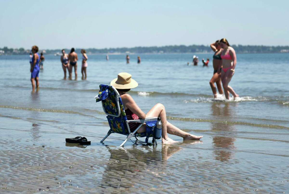 People relax on the beach at Greenwich Point Park in Old Greenwich, Conn. Wednesday, June 30, 2021.
