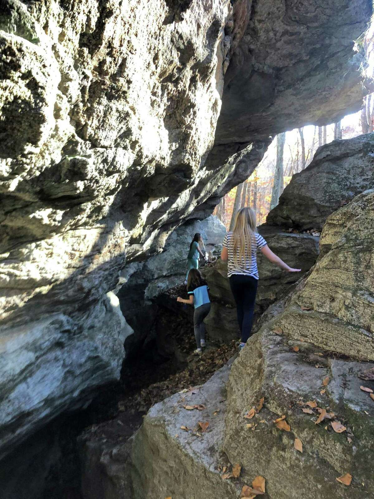Children explore Fat Man's Queeze, a rock formation left over from a glacier.