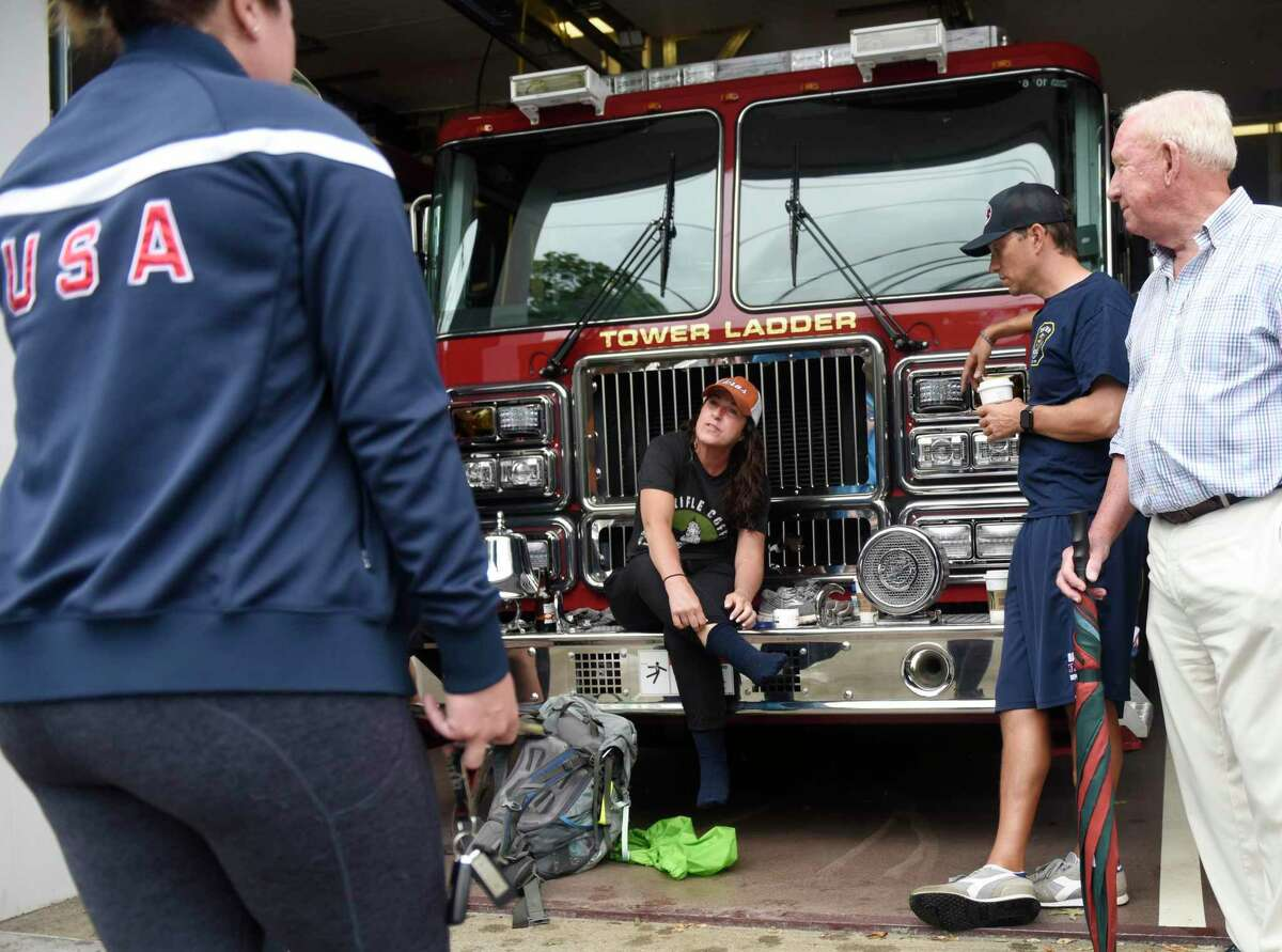 Denise Olsen, of Manasquan, N.J., tends to her aching feet during a pit stop from the Boston to World Trade Center Heroes Hike at the Darien Fire Department in Darien, Conn. Thursday, Sept. 9, 2021. Olsen, who lost her husband in 9/11, Stokes, an Army veteran, and Richter, a high school student, have spent the last 12 days hiking from Boston Logan International Airport to the World Trade Center memorial. The group plans to conclude their 225 mile journey by arriving at the site of the World Trade Centers by 8:46 a.m. on September 11.