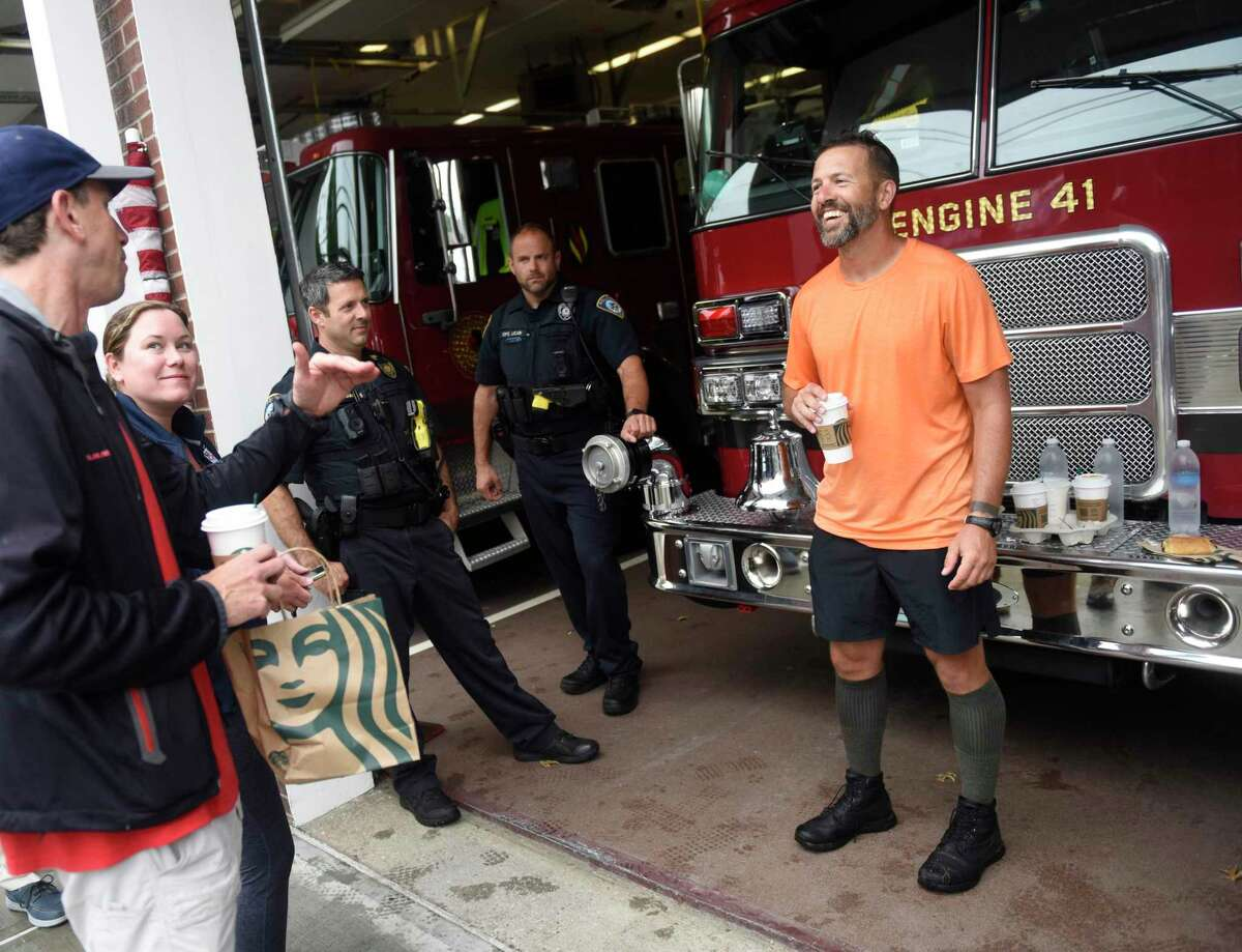 Daniel Stokes, right, of Seattle, is greeting by police and firefighters during a pit stop from the Boston to World Trade Center Heroes Hike at the Darien Fire Department in Darien, Conn. Thursday, Sept. 9, 2021. Olsen, who lost her husband in 9/11, Stokes, an Army veteran, and Richter, a high school student, have spent the last 12 days hiking from Boston Logan International Airport to the World Trade Center memorial. The group plans to conclude their 225 mile journey by arriving at the site of the World Trade Centers by 8:46 a.m. on September 11.