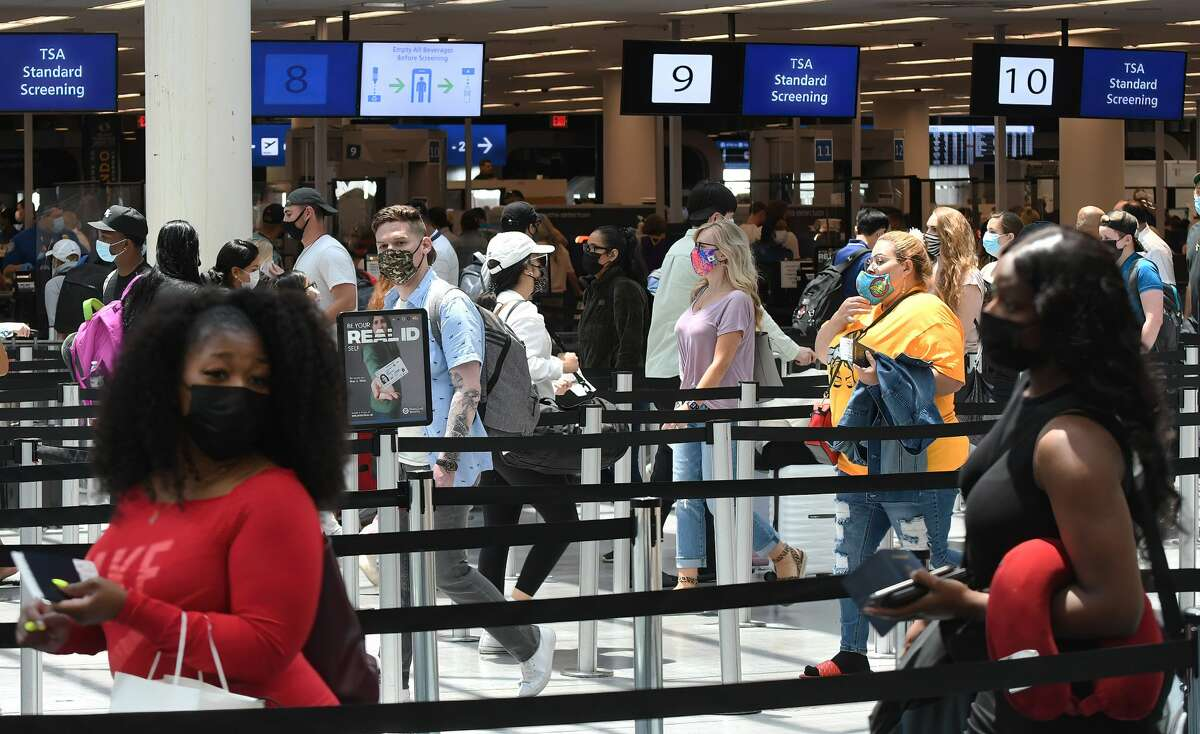 FILE - Travelers wait in line at a Transportation Security Administration screening checkpoint at Orlando International Airport on the Friday before Memorial Day. (Photo by Paul Hennessy/SOPA Images/LightRocket via Getty Images)