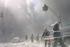 Emergency crews survey the damage after the fall of the twin towers on September 11, 2001 in New York City. (AP Photo/Shawn Baldwin)