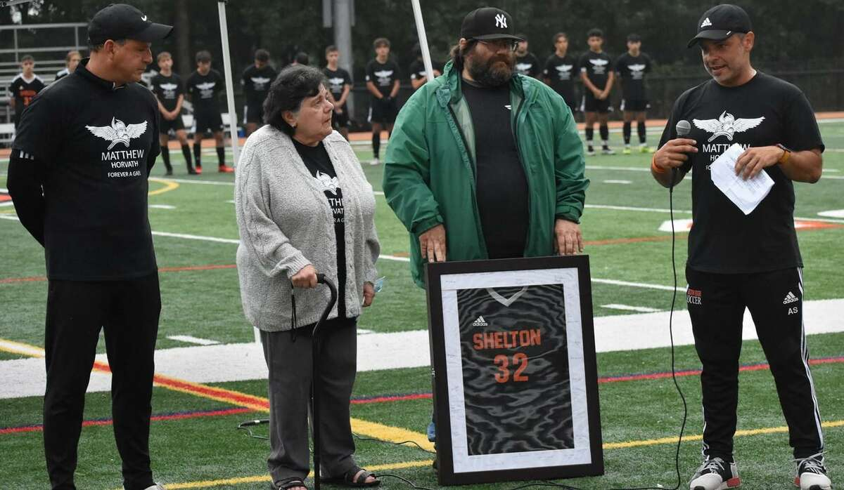Shelton assistant boys' soccer coach Augie Sevilliano speaks to Matt Horvath's father Matthew and grandmother Patt during the ceremony to retire Horvath's jersey #32. Horvath, a 2021 graduate, died in July following a watercraft accident. He was a three-year starter for coach Isaac Montalvo and the Gaels.