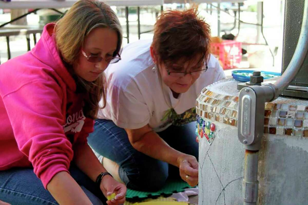 In this file photo from 2013, Christina Hatfield and artist Patricia Terpstra work together on a mosaic in Pocket Park as part of an Artworks summer camp. (Pioneer file photo)