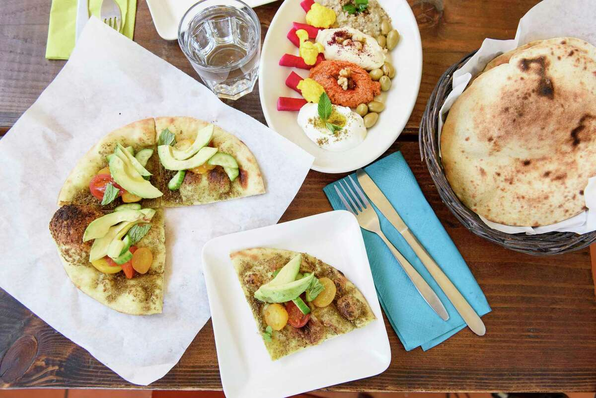 The za'atar man'oushe, left, mezze combo, and pita bread at Reem's in Oakland. The restaurant is moving to a new location in Fruitvale.