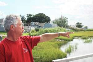 Rick Tanasi points to where he says water flowing under the Old Saybrook bridge has eroded marshland over the last decade.
