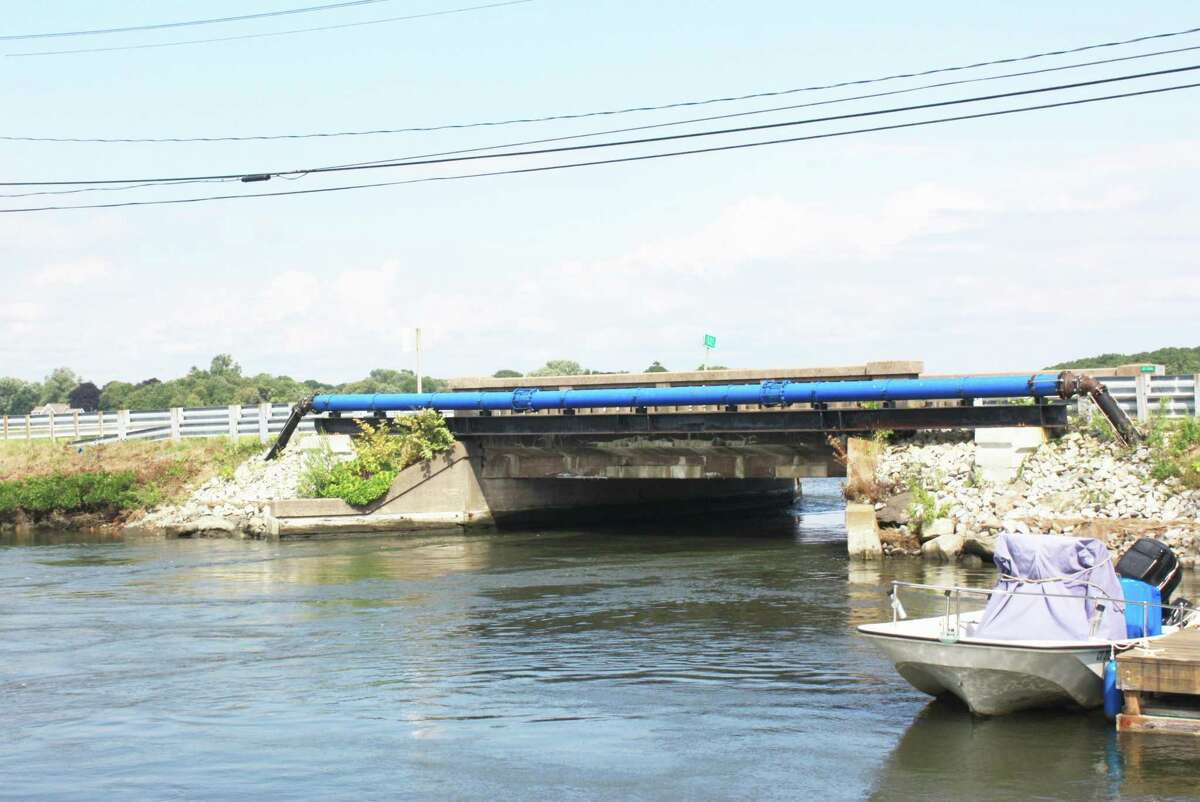 Water races under Bridge No. 01386 in Old Saybrook. Residents complain that the bridge, which is scheduled to be replaced, directs strong currents toward marshland and their homes, causing erosion.