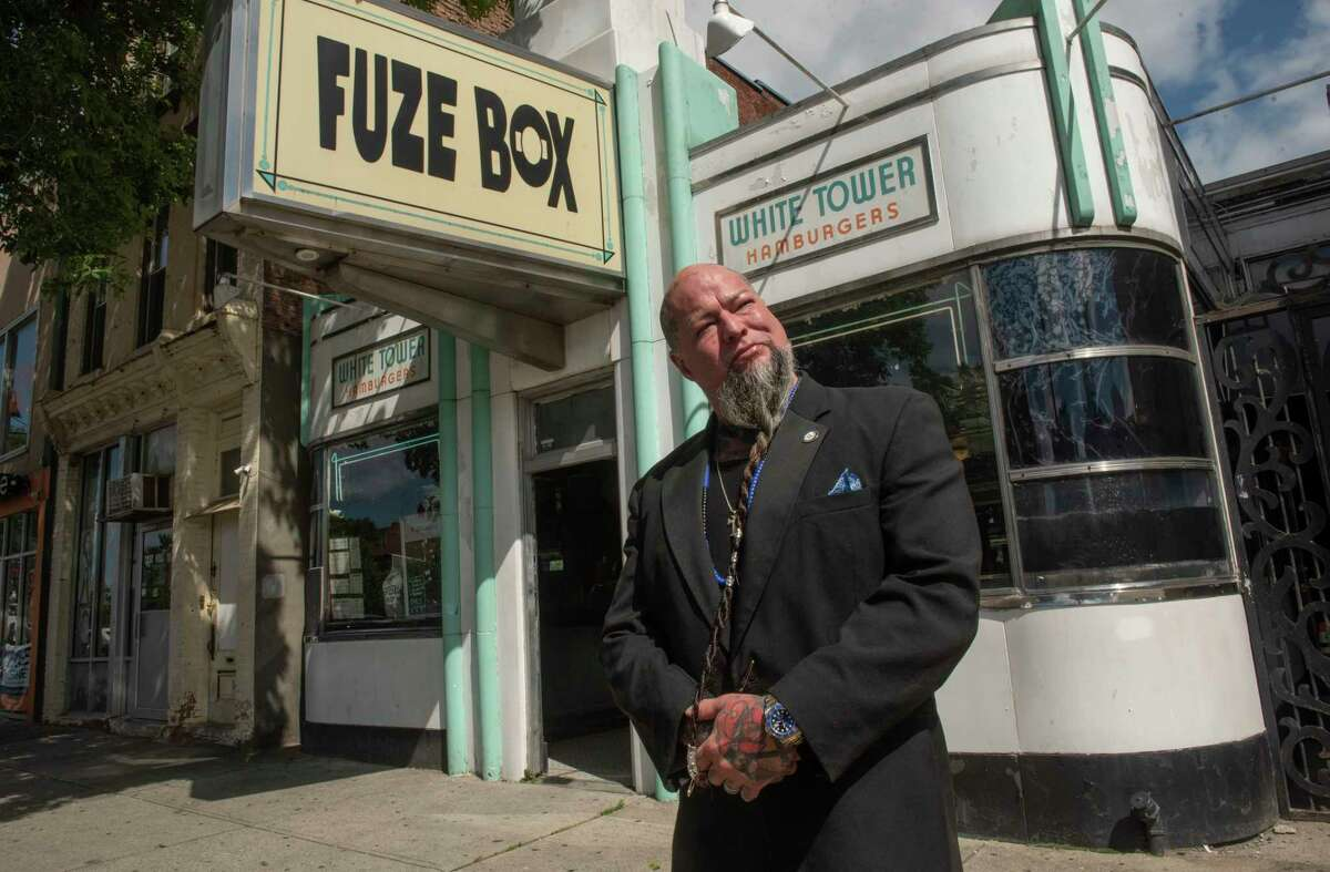 """Entrepreneur William """"Tragedy"""" Yager stands in front of the Fuze Box building on Friday, Sept. 10, 2021 in Albany, N.Y. Yager, who owns barbershops, tattoo parlors, a laundromat and mead bar, has purchased the building and intends to revitalize it."""