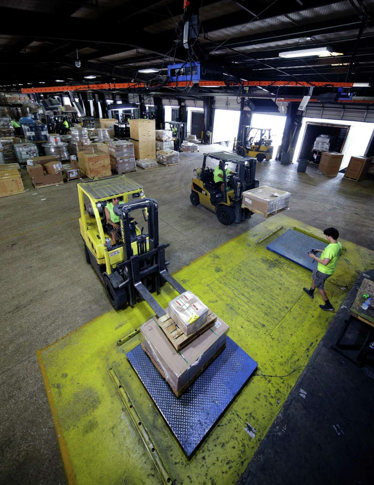 The Cargo Spectre apparatus, the orange bar (at top) suspended from the ceiling over blue weight scales where freight pallets are placed by forklifts, has sensors and lights to fully automate instantaneous weight and dimension data of the pallets in the warehouse at World Trade Distribution Thursday, Aug. 12, 2021 in Houston, TX.