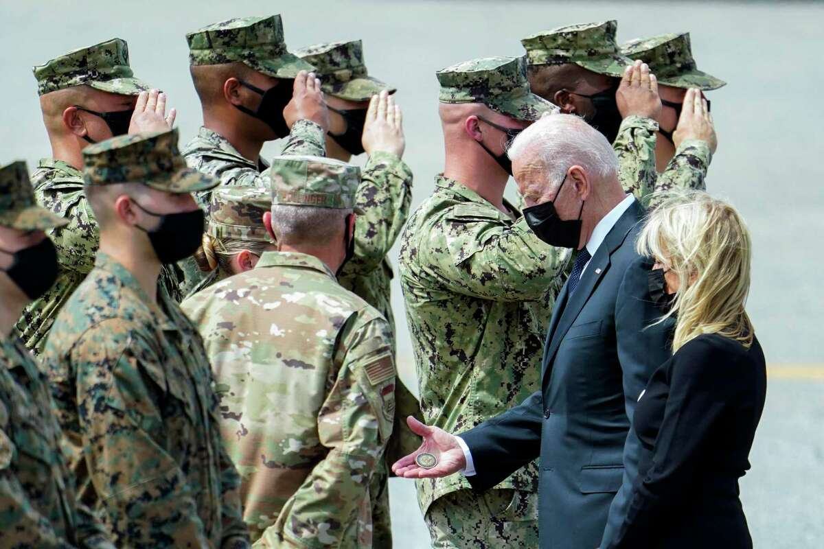 President Joe Biden holds a presidential challenge coin as he speaks with members of the Air Force as service members killed in Afghanistan return to Dover Air Force Base. Readers have been split on the withdrawal and end to the war in Afghanistan.