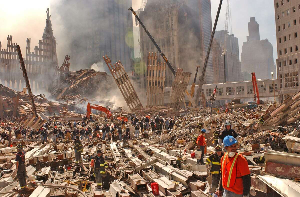 First responders go through the wreckage at ground zero. Twenty years later, we are only beginning to comprehend how the attacks changed us.