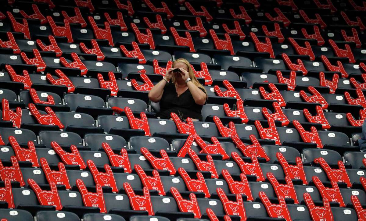 A fan seated among the foam hands in the stands during warmups before the start of an NFL preseason football game at NRG Stadium, Saturday, August 28, 2021.