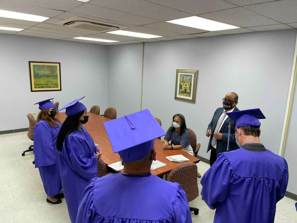 Case manager Jackie Aguirre and Court Manager Roberto Ruiz brief the four Reflejo graduates before their ceremony. The new Bexar County court gives a second chance to adults with a history of substance abuse who have also been charged with misdemeanor domestic violence.