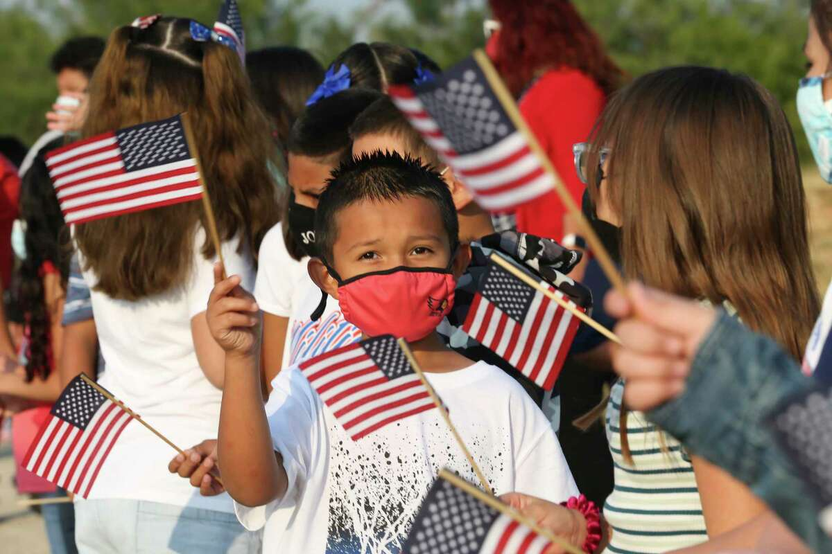 Heritage Elementary students wave flags during a 9/11 ceremony Friday, Sept. 10, 2021.