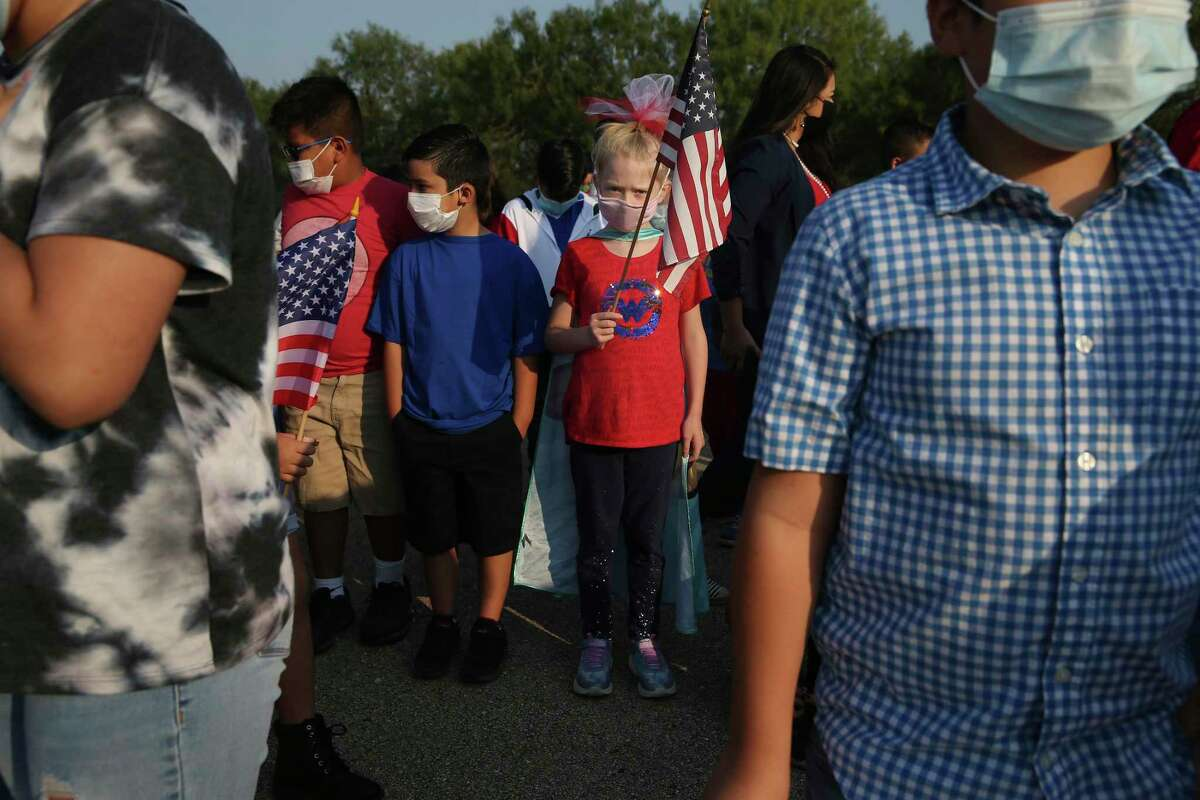 With flag in hand and wearing her Wonder Woman costume, Jocelyn Jordan, 8, participates in the 9/11 Remembrance Day Ceremony at Heritage Elementary School on Friday.