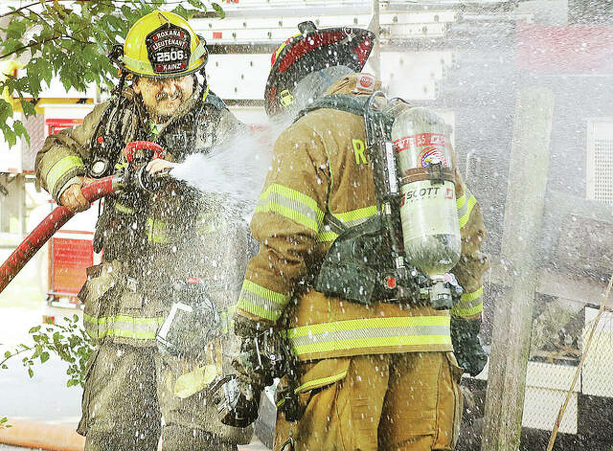 An East Alton firefighter washes insulation and other debris from a Roxana firefighter's turnout gear at a house fire Friday morning at 108 Lakeside Drive in East Alton. No injuries were reported.