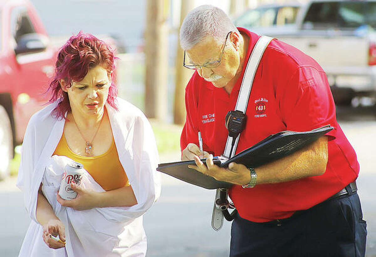 East Alton Fire Chief Tim Quigley talks with the resident of the house which caught fire Friday on Lakeside Drive.