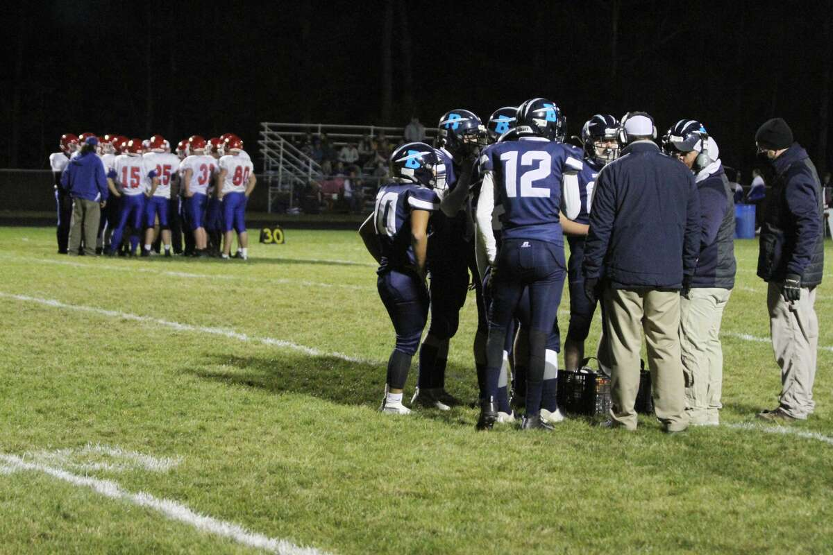 Brethren varsity football huddles up prior to taking the field against Manistee Catholic Central.