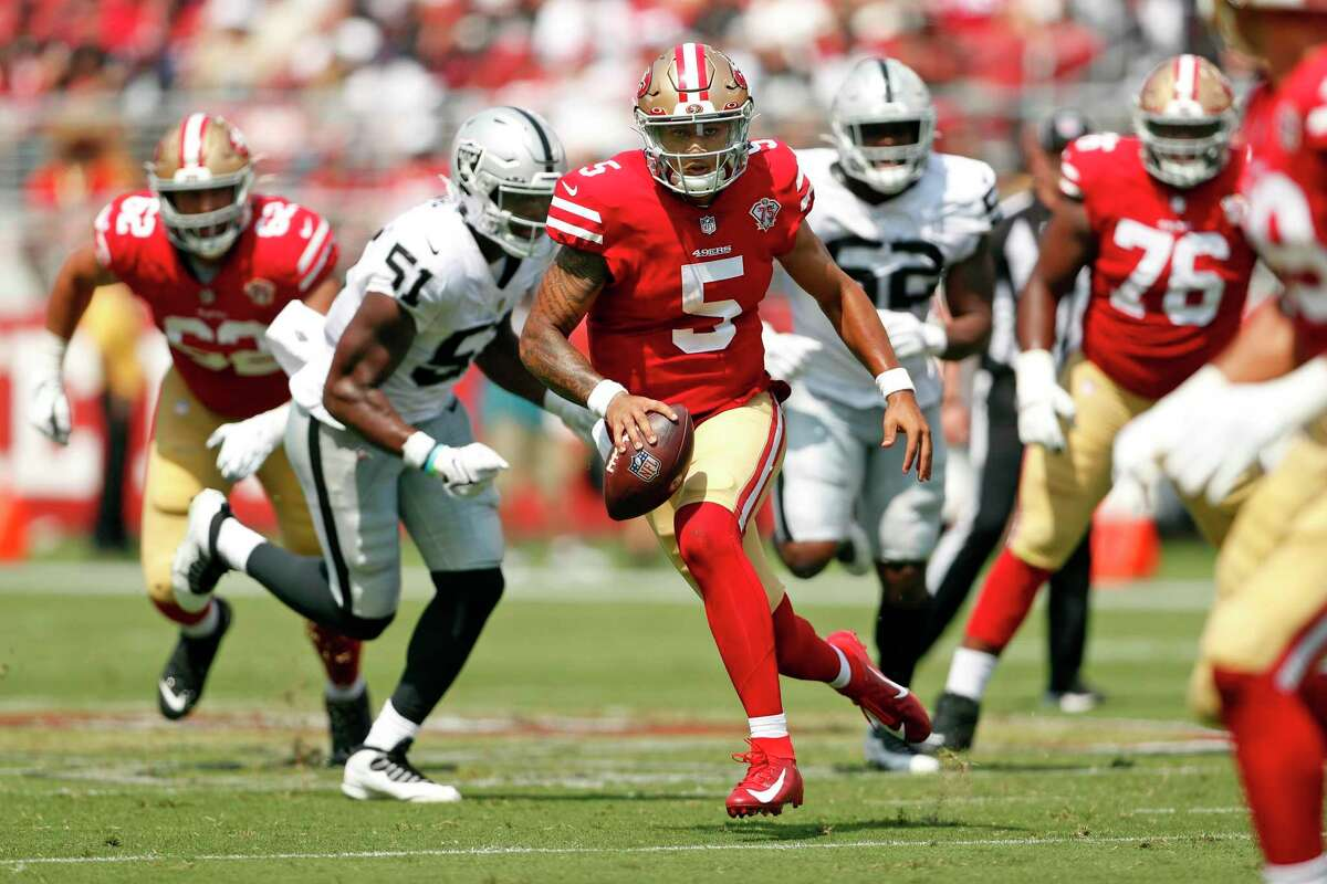 San Francisco 49ers' Trey Lance scrambles for a 1st down in 2nd quarter against Las Vegas Raiders during NFL preseason game at Levi's Stadium in Santa Clara, Calif., on Sunday, August 29, 2021.