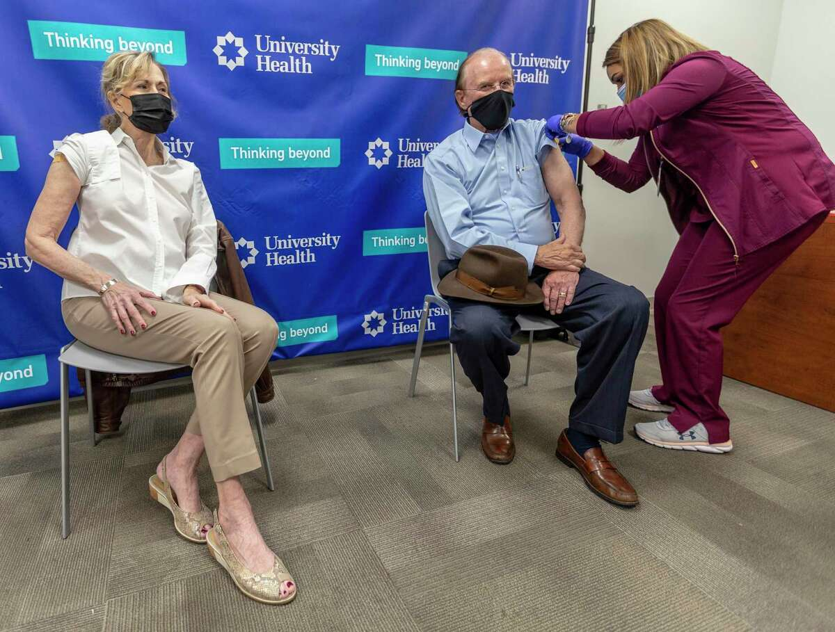 Bexar County Judge Nelson Wolff, center, gets vaccinated and rocks a mask in December. He's trying to keep you healthy and free from COVID, so quit harassing him.