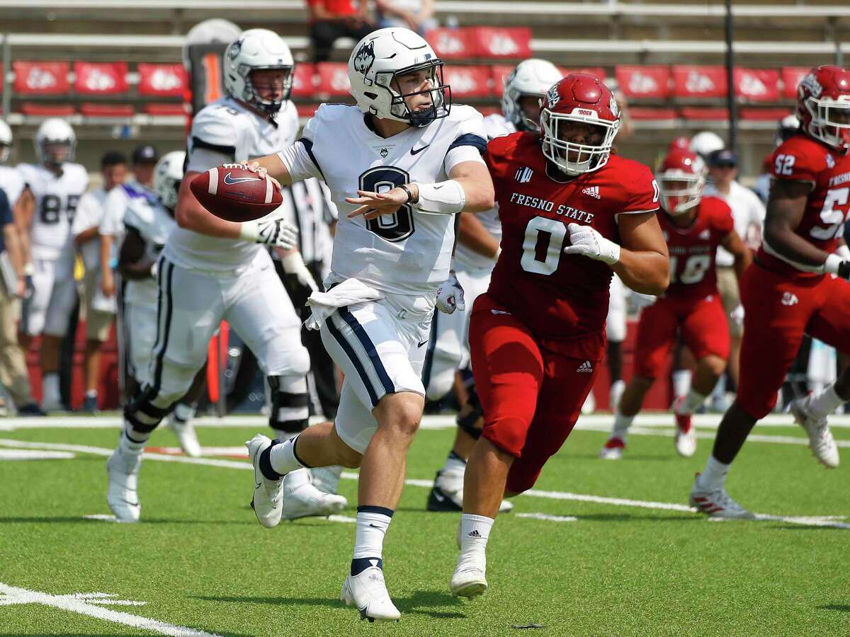 Connecticut quaterback Steven Krajewski rolls out to pass against Fresno State during the second half of an NCAA college football game in Fresno, Calif., Saturday, Aug. 28, 2021. (AP Photo/Gary Kazanjian)