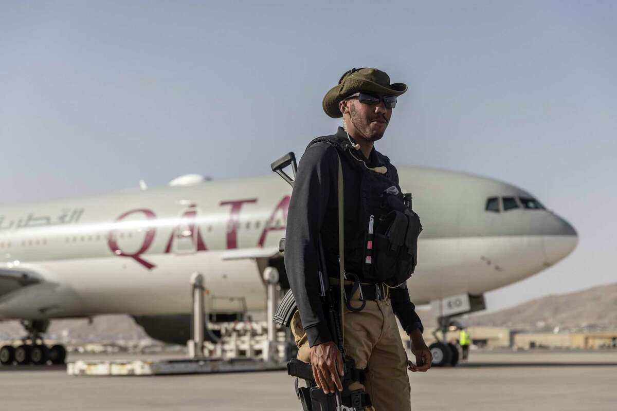 A Qatari security officer stands guard near a commercial Qatari passenger flight at Hamid Karzai International Airport in Kabul, Afghanistan, Sept. 9, 2021. The plane, the first international passenger flight to depart Afghanistan since the frenzied U.S. military evacuation late last month, took off on Thursday, with more than 100 foreigners - including Americans - able to leave the country after days of anxious uncertainty. (Victor J. Blue/The New York Times)