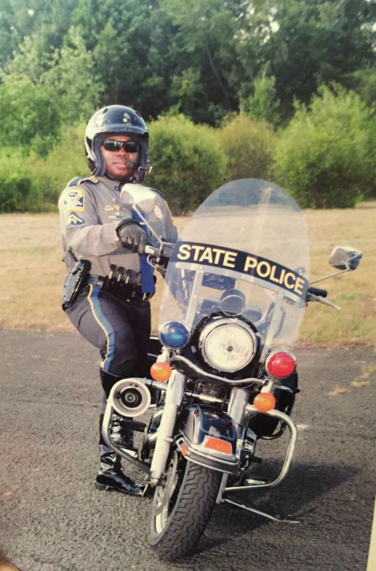 Trooper Walter Greene, Jr., stands next to his state police motorcycle in this updated photo.