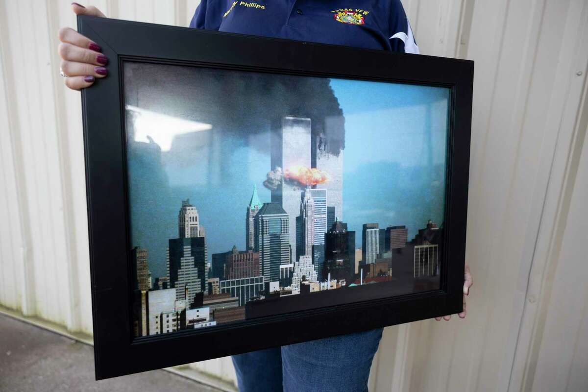 Marcey Phillips, post junior vice commander, poses for a portrait with an image of the 9/11 terrorists attack at the VFW Post 4709, Wednesday, Sept. 8, 2021, in Conroe. Phillips served in Iraq upon joining the U.S. Army shortly following the Sept. 11, 2001 terrorist attacks and after becoming a young mother.