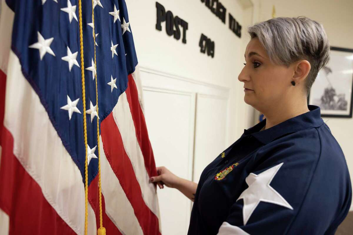 Marcey Phillips, post junior vice commander, straightens the American flag at the VFW Post 4709, Wednesday, Sept. 8, 2021, in Conroe. Phillips served in Iraq upon joining the U.S. Army shortly following the Sept. 11, 2001 terrorist attacks and after becoming a young mother.