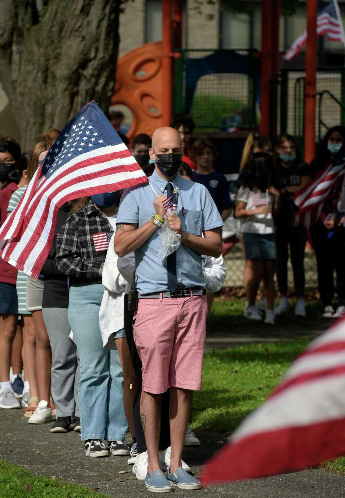 Eighth grade teacher David Bongiorno leads students from St. Joseph School, in Danbury, to each plant a flag during a September 11th 20th Anniversary Ceremony at the school on Friday Morning. September 10, 2021, Danbury, Conn.