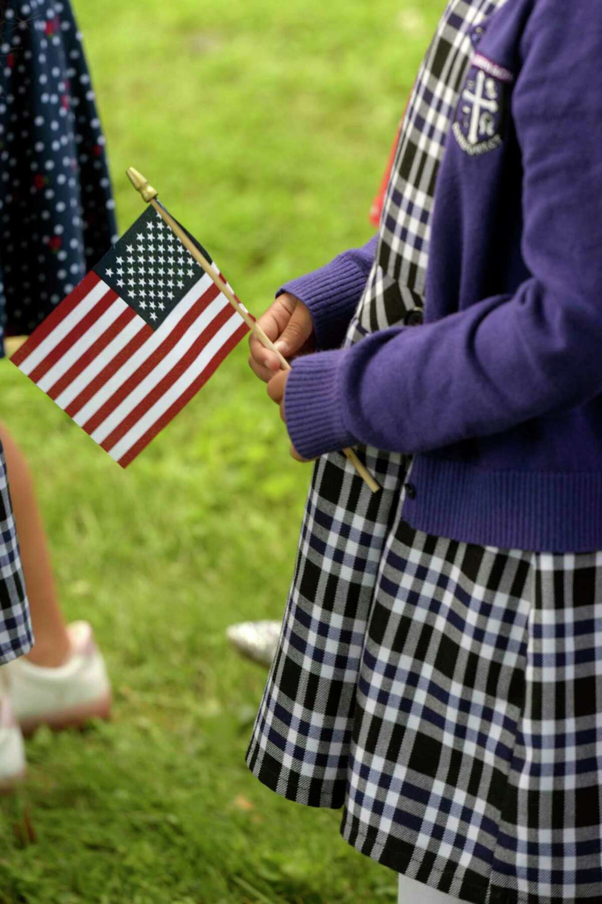 A student holds a flag during a September 11th 20th Anniversary Ceremony at St. Joseph School, Friday Morning. September 10, 2021, Danbury, Conn.