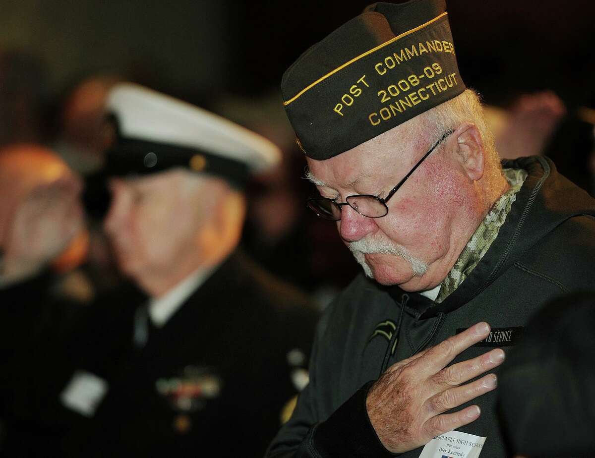 A 2017 file photo showing Dick Kennedy bowing his head during the singing of the National Anthem at a Veterans Day Celebration ceremony at Bunnell High School in Stratford, Conn. Kennedy died Saturday, Sept. 4 at the age of 76.