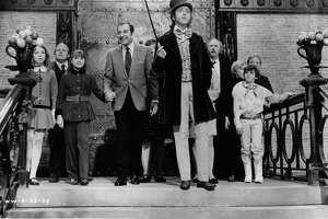 Julie Dawn Cole, Roy Kinnear, Denise Nickerson, Leonard Stone, Ursula Reit, Gene Wilder, Jack Albertson, Peter Ostrum, Paris Themmen, and Michael Bollner at the top of a staircase in a scene from the film 'Willy Wonka & the Chocolate Factory', directed by Mel Stuart, 1971. (Photo by Paramount/Getty Images)
